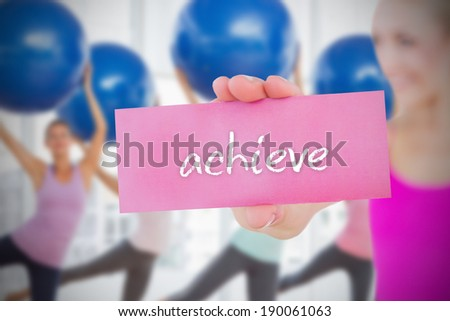 Fit blonde holding card saying achieve against fitness class in gym - stock photo
