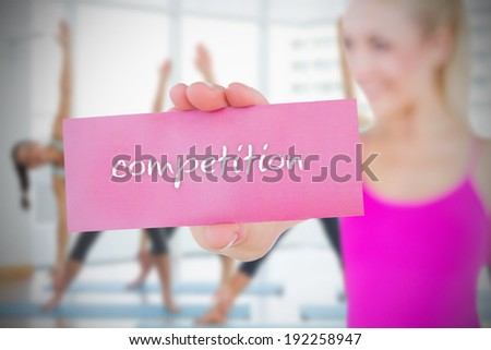 Fit blonde holding card saying competition against fitness class in gym - stock photo