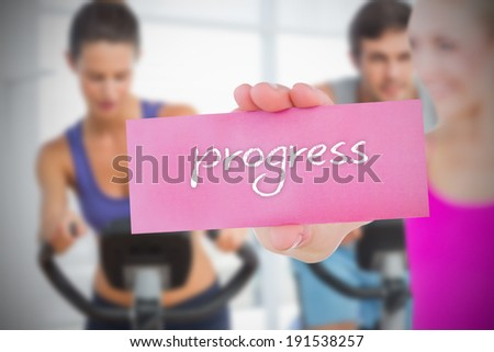 Fit blonde holding card saying progress against fitness class in gym - stock photo