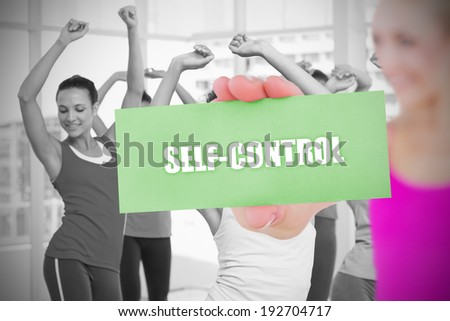Fit blonde holding card saying self control against fitness class in gym - stock photo