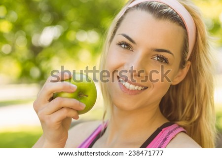 Fit blonde holding green apple on a sunny day - stock photo