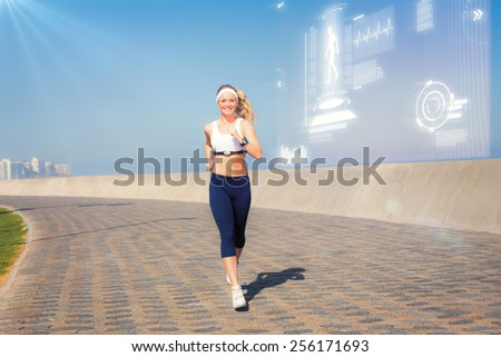 Fit blonde jogging on the pier against fitness interface - stock photo