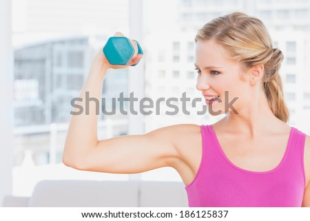 Fit blonde lifting dumbbell and flexing at home in the living room - stock photo