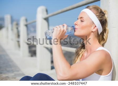 Fit blonde sitting on the pier drinking water on a sunny day - stock photo