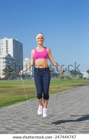 Fit blonde skipping rope on the pier on a sunny day - stock photo