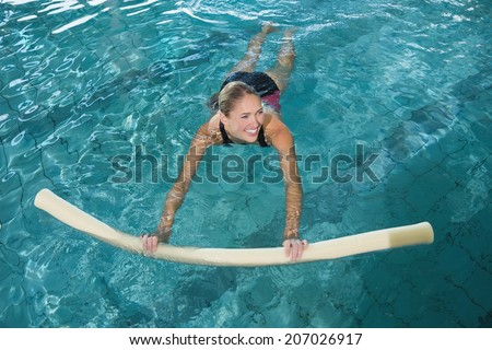 Fit blonde swimming with foam roller in swimming pool at the leisure centre - stock photo