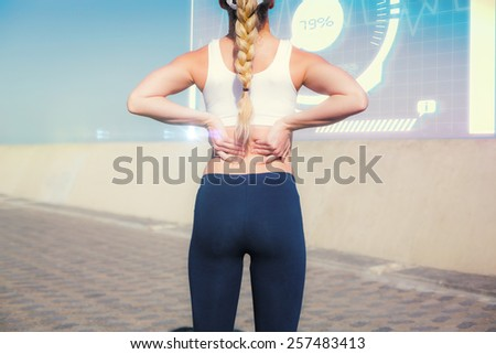Fit blonde touching her back on the pier against fitness interface - stock photo