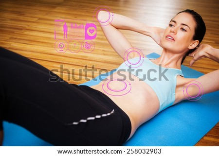 Fit brunette doing sit ups in fitness studio against fitness interface - stock photo
