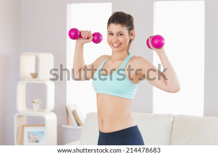 Fit brunette holding dumbbells smiling at camera at home in the living room - stock photo