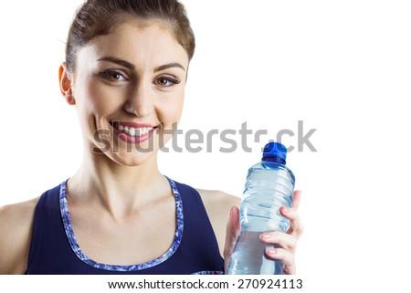 Fit brunette holding water bottle on white background - stock photo