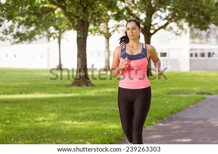 Fit brunette jogging in the park on a sunny day - stock photo