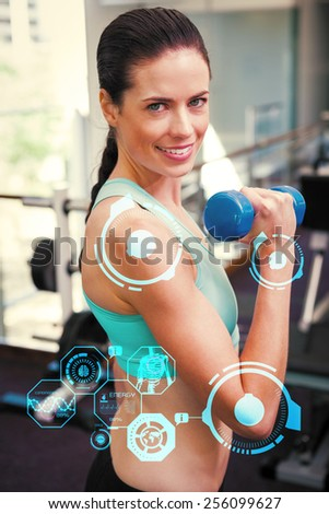 Fit brunette lifting blue dumbbell against fitness interface - stock photo