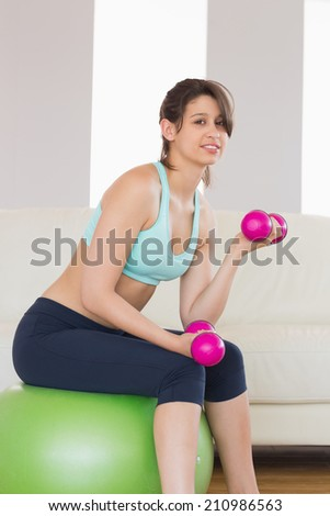 Fit brunette sitting on exercise ball lifting hand weights at home in the living room - stock photo
