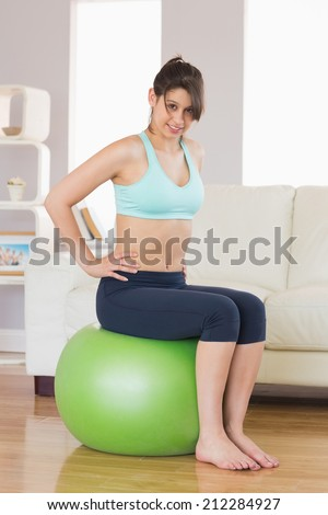 Fit brunette sitting on exercise ball smiling at camera at home in the living room - stock photo