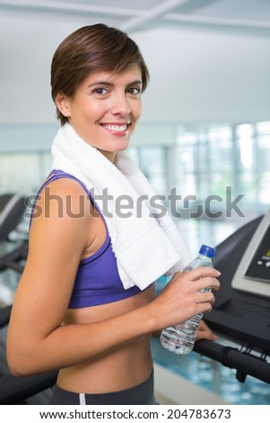 Fit brunette smiling at camera on the treadmill at the gym - stock photo