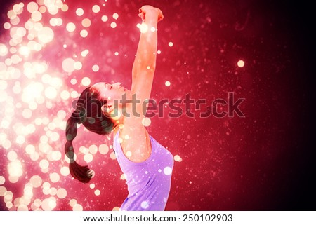 Fit brunette stretching her arms against light design shimmering on red - stock photo