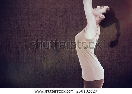 Fit brunette stretching her arms against weathered surface - stock photo