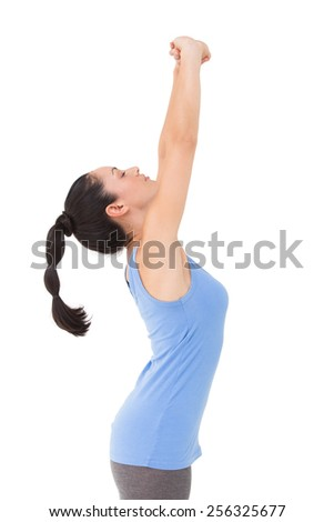 Fit brunette stretching her arms on white background - stock photo