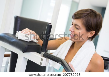 Fit brunette wiping down bench at the gym - stock photo
