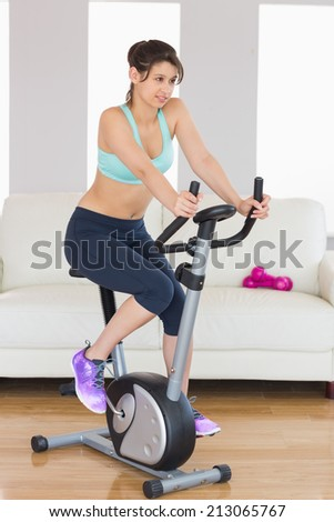 Fit brunette working out on exercise bike at home in the living room - stock photo
