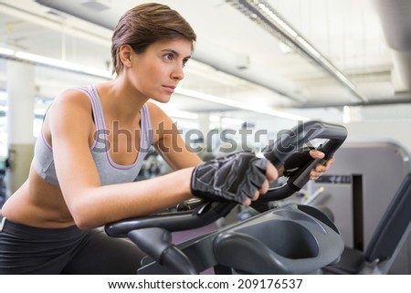 Fit brunette working out on the exercise bike at the gym - stock photo