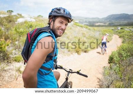 Fit couple cycling on mountain trail man smiling at camera on a sunny day - stock photo
