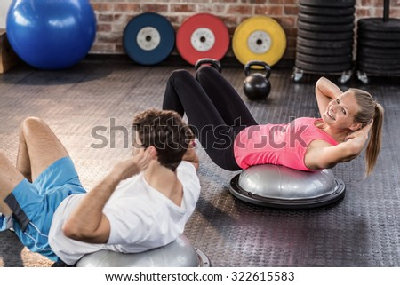 Fit couple doing abdominal crunches in crossfit gym - stock photo