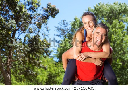 Fit couple having fun in the park on a sunny day - stock photo
