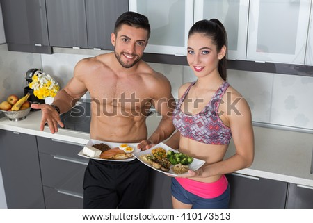 fit couple in the kitchen; animal versus plant proteins: one plate with beef, eggs, salmon, cheese and chicken grill and another with nuts, mushrooms, broccoli, lentil, hummus and quinoa - stock photo