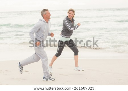 Fit couple jogging together at the beach - stock photo