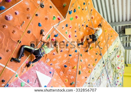 Fit couple rock climbing indoors at the gym - stock photo