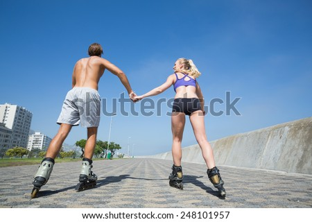 Fit couple rollerblading together on the promenade on a sunny day - stock photo