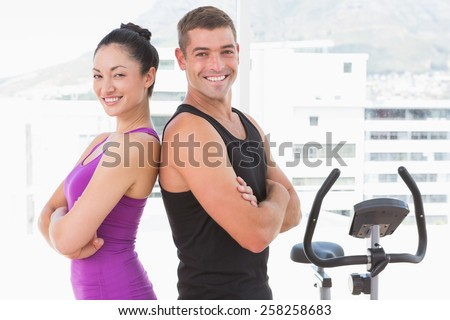 Fit couple smiling at camera with arms crossed in fitness studio - stock photo