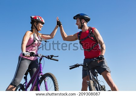 Fit cyclist couple standing at the summit high fiving on a sunny day - stock photo