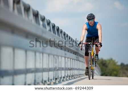 fit cyclist riding on race bike - stock photo