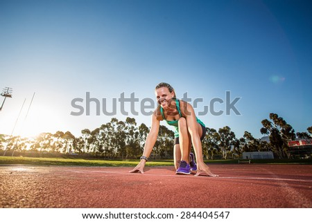 Fit female athlete standing / sitting at the start line to a sprint on a tartan athletics track with dramatic late afternoon lighting. - stock photo