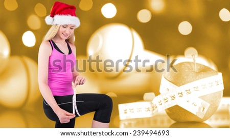 Fit festive young blonde measuring her thigh against orange vignette - stock photo