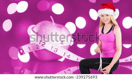 Fit festive young blonde measuring her thigh against pink - stock photo