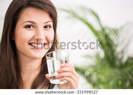 Fit girl drinking glass of mineral water - stock photo