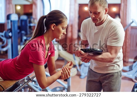 Fit girl exercising on facilities with her trainer near by - stock photo
