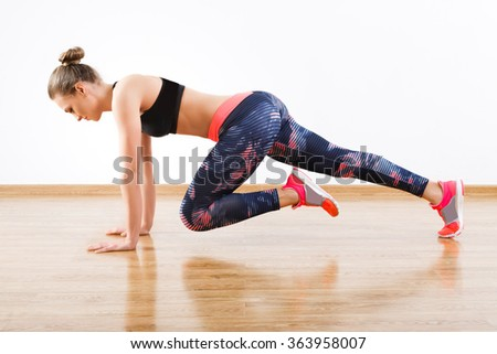 Fit girl with dark hair wearing pink snickers, dark leggings and black short top doing full plank with bent leg at gym, fitness, white wall and wooden floor. - stock photo