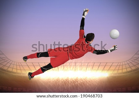 Fit goal keeper jumping up against large football stadium with spotlights at sunrise - stock photo