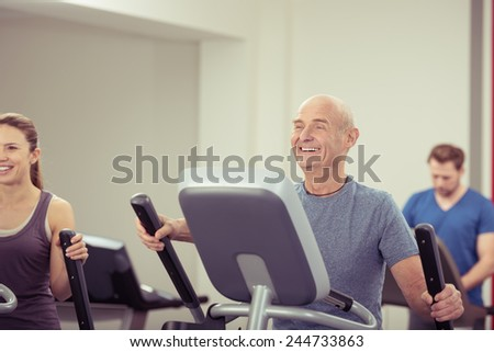 Fit handsome elderly balding man working out in a gym on their equipment with a female friend smiling happily in enjoyment in a healthy lifestyle concept - stock photo