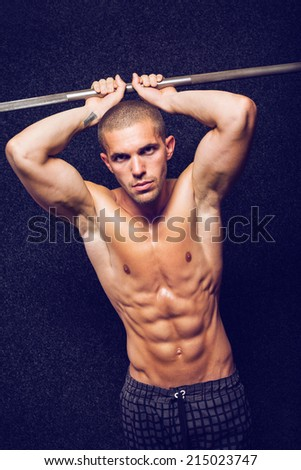 Fit handsome shirtless young Caucasian man in gym holding his hands up showing biceps looking at camera. Serious attractive young fitness guy against dark background. - stock photo