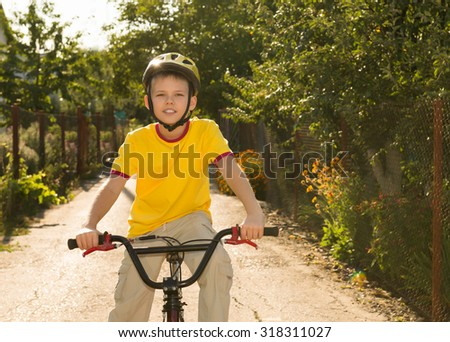 Fit happy teen boy on a bike on a countryside road. Child riding a bike outdoors in summer.  Healthy lifestyle concept.  - stock photo
