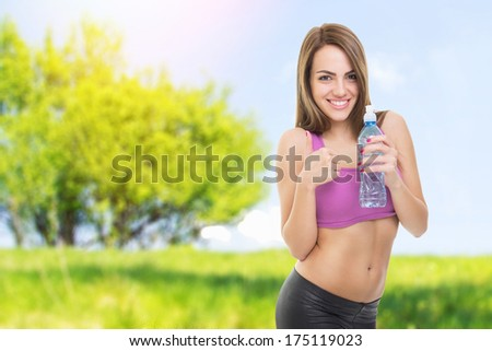 Fit happy young beautiful Caucasian woman outdoors fitness workout. Woman holding bottle of water and gesturing thumbs up. Fitness and healthy lifestyle concept. - stock photo