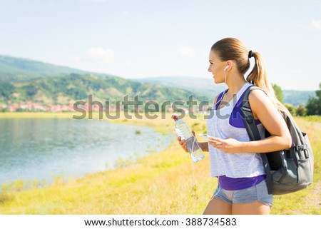 Fit happy young blonde Caucasian woman hiking in nature by the lake on sunny summer day. Girl with water bottle and backpack in nature walking and relaxing. Mild retouch, no filter, natural light - stock photo
