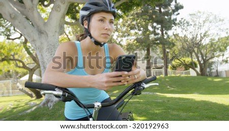 Fit healthy asian woman riding bike outdoors - stock photo