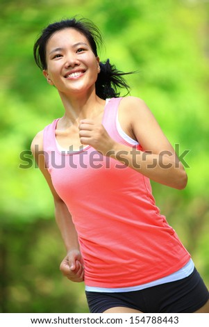 fit healthy asian woman runner running in park - stock photo