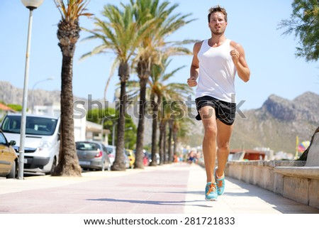 Fit male runner running outside on boardwalk. Young man model training fitness jogging on Mallorca beach city outdoors in summer sun. Palms in background. Healthy lifestyle. - stock photo